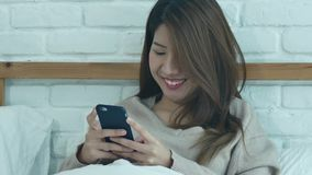 Happy Asian women are using smart phone on the bed in morning. Asian woman in bed checking social apps with smartphone. Smiling woman surfing net with stock video footage