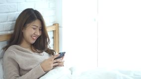 Happy Asian women are using smart phone on the bed in morning. Asian woman in bed checking social apps with smartphone. Smiling woman surfing net with stock video