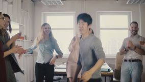 Happy Asian young businessman dancing at casual office party. Japanese employee celebrates victory with colleagues 4K. stock footage