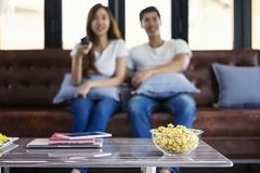 Happy asian young couple loving on the couch watching a movie to. Gether,Woman holding remote and her husband sittind next to her.Close up popcorn Royalty Free Stock Photography