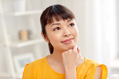 Happy asian young dreaming woman face at home Stock Photography