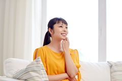 Happy asian young dreaming woman at home Stock Photography