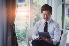 Happy asian young handsome businessman using tablet. Royalty Free Stock Image