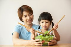 Asian Young Mother and little girl cooking salad. royalty free stock images