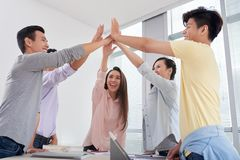 We will achieve everything. Happy Asian young people giving each other high five Stock Photography