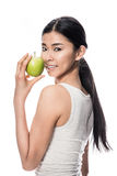 Happy Asian young woman holding a green apple. Happy Asian young woman looking at camera while holding a green apple against white background Royalty Free Stock Images