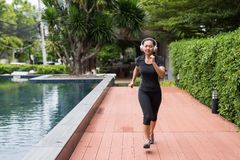 Chinese young woman run in park. Happy Asian young woman jogging or running and listening online music by bluetooth earphone. Cute Chinese girl run in park near stock photography