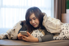 Happy asian young woman lying using smart phone Royalty Free Stock Photography
