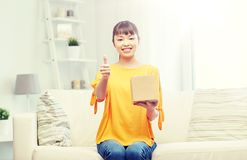 Happy asian young woman with parcel box at home Stock Image