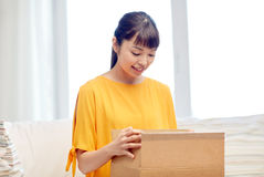 Happy asian young woman with parcel box at home Stock Photos