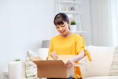 Happy asian young woman with parcel box at home Royalty Free Stock Image