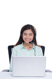 Happy asian young woman sitting and working with laptop using headset in office Royalty Free Stock Images