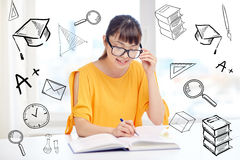 Happy asian young woman student learning at home. People, education, high school and learning concept - happy asian young woman student with book and notepad Royalty Free Stock Photo