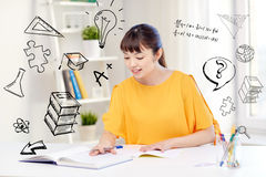Happy asian young woman student learning at home. People, education, high school and learning concept - happy asian young woman student with book and notepad Royalty Free Stock Image