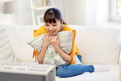 Happy asian young woman watching tv at home Royalty Free Stock Image