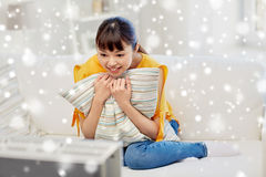 Happy asian young woman watching tv at home. Television, entertainment, leisure and people concept - happy asian young woman watching tv at home over snow Royalty Free Stock Photo