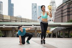 Running winner and loser in city. Happy Asian young women winner raise gold trophy to celebrate running victory while male loser runner fall on floor or footpath Royalty Free Stock Images