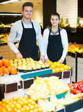 Happy assistants demonstrating assortment. Happy shopping assistants demonstrating assortment of grocery shop royalty free stock image