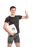 Happy athlete holding a weight scale Stock Image