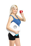 Happy athlete holding a weight scale and red apple Royalty Free Stock Photos