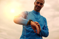 Happy athlete is looking at smart watch. Sunlight effect Stock Photos
