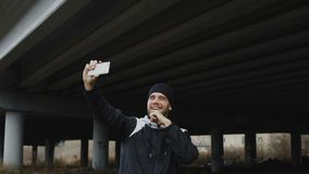 Happy athlete man taking selfie portrait with smartphone after boxing training in urban outdoors location in winter stock video footage