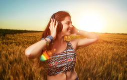 Happy  athletic caucasian young woman  listening to music. Touch with the hands of  black headphones on a sunset background in a wheat field Stock Images