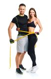 Happy athletic couple - man and woman with measuring tape on the Royalty Free Stock Photos
