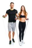 Happy athletic couple - man and woman with with ropes on the white. Happy athletic couple - men and women with with ropes on the white background royalty free stock image
