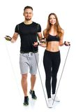 Happy athletic couple - man and woman with with ropes on the white. Happy athletic couple - men and women with with ropes on the white background royalty free stock photos