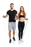 Happy athletic couple - man and woman with with ropes on the white. Happy athletic couple - men and women with with ropes on the white background stock image