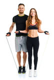 Happy athletic couple - man and woman with with ropes on the white. Happy athletic couple - men and women with with ropes on the white background stock photography