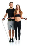 Happy athletic couple - man and woman with with ropes on the white. Happy athletic couple - men and women with with ropes on the white background stock photo