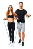 Happy athletic couple - man and woman with ropes on the white. Happy athletic couple - men and women with ropes on the white background stock photography
