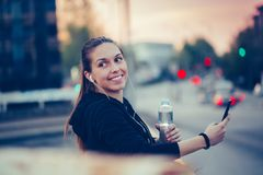 Happy athletic girl taking a break after work out and listening music while using smart phone. Young woman relaxing on the bridge, after jogging. She using her royalty free stock image