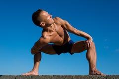 Happy Athletic man doing yoga asanas in the park at sunny day Royalty Free Stock Photos