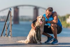 Sportswoman with dog on quay. Happy athletic sportsman hugging golden retriever dog on quay Stock Image