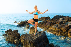 Happy athletic woman practicing yoga on the rocks by the sea Stock Photos