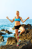 Happy athletic woman practicing yoga on the rocks by the sea Royalty Free Stock Image