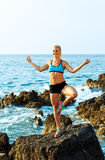 Happy athletic woman practicing yoga on the rocks by the sea Royalty Free Stock Photos