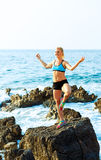 Happy athletic woman practicing yoga on the rocks by the sea Royalty Free Stock Photography