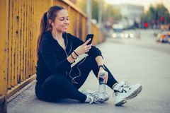 Happy athletic woman taking a break after work out and listening music while using smart phone. Young woman relaxing after jogging. She using her smart phone and royalty free stock image