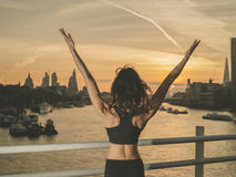 Happy athletic young woman wih arms raised at sunrise Stock Photos