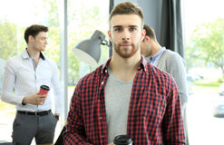 Happy attracive young businessman drinking coffee in office. Stock Photos