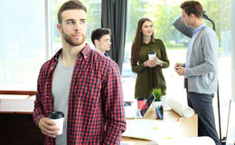 Happy attracive young businessman drinking coffee in office. Royalty Free Stock Photo