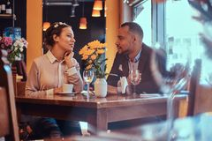 Happy attractive African-American couple in love having a great time together in a restaurant at their dating. A royalty free stock photography