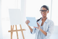Happy attractive artist using her tablet pc Royalty Free Stock Photo