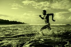 Happy and attractive black afro American man with fit healthy and muscular body running on beach sea water having fun enjoying royalty free stock images
