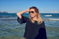 Happy attractive blond woman wearing sunglasses. At the seaside on a sunny day posing in front of the ocean with her hair blowing in the sea breeze grinning to stock image