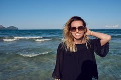 Happy attractive blond woman wearing sunglasses. At the seaside on a sunny day posing in front of the ocean with her hair blowing in the sea breeze grinning at stock image